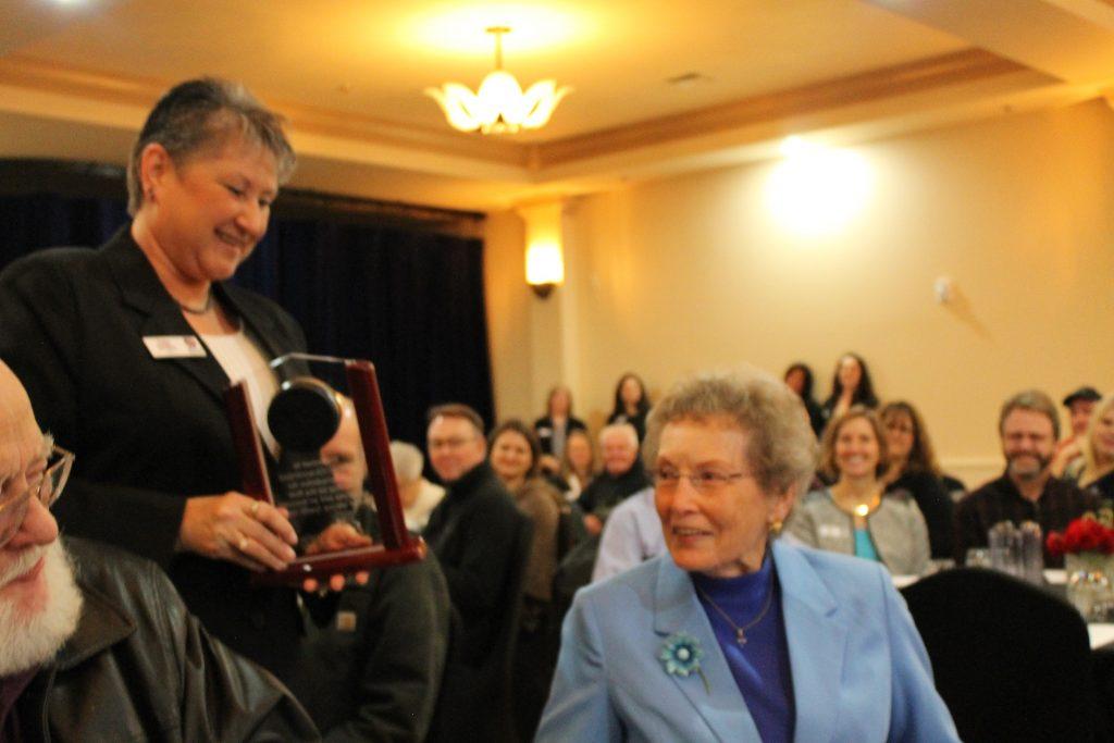 WCU CMO Debi Smiley presents an award to Eileen