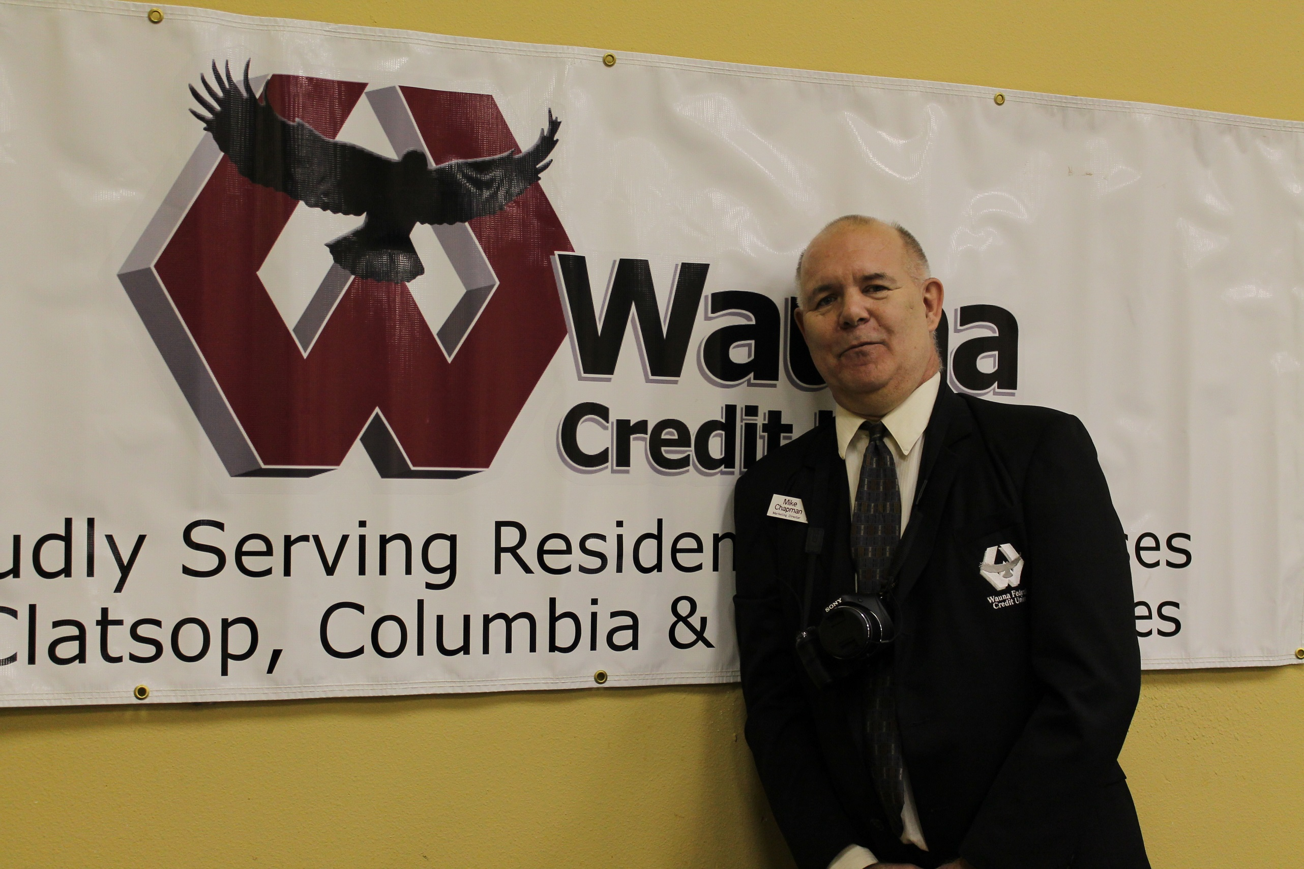 Mike poses against a Wauna banner at the annual meeting